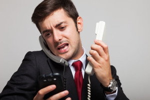 32259023 - stressed businessman talking on many phones at once